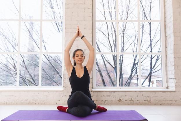 Junges schönes mädchen, das yoga gomukhasana asana tut. hände hoch, vorderansicht Premium Fotos