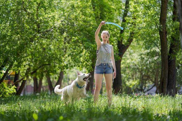 Junges schönes mädchen, das zu ihrem hund in einem park bei sonnenuntergang wirft Premium Fotos