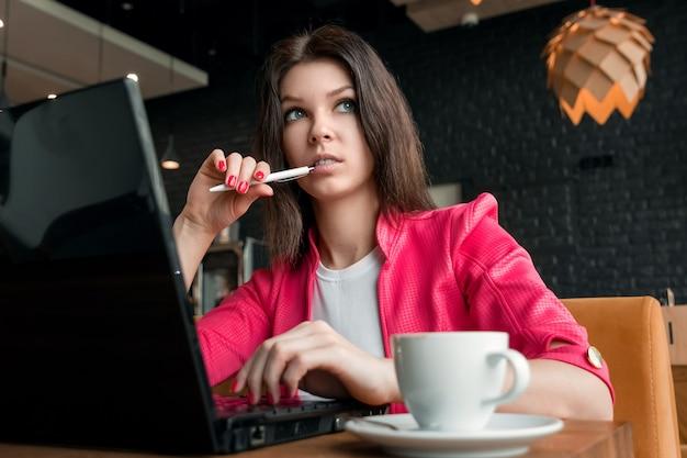 Junges, schönes mädchen, geschäftsfrau, im café sitzend und arbeiten an laptop Premium Fotos
