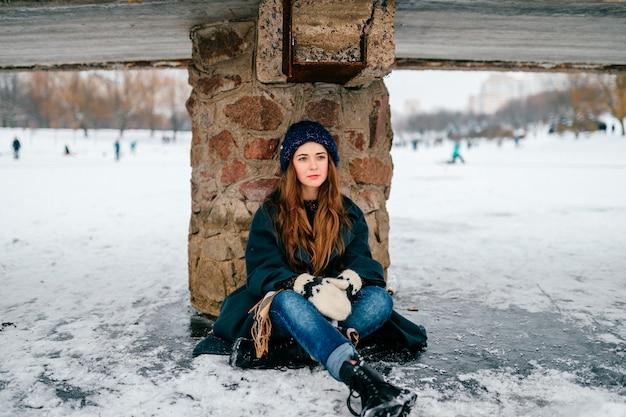 Junges schönes mädchen in der stilvollen kleidung mit dem langen haar, das unter brücke auf eis auf gefrorenem see am kalten wintertag im stadtpark sitzt. Premium Fotos