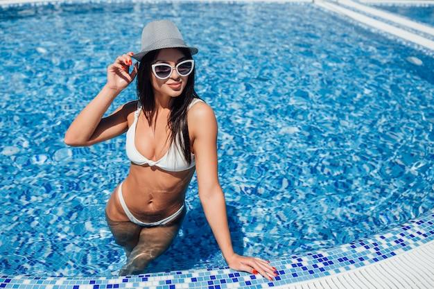 Junges schönes mädchen in einem weißen badeanzug, in einer sonnenbrille und in einem hut mit einer schönen zahl Premium Fotos