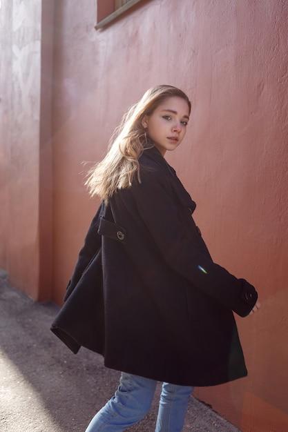 Junges schönes mädchen mit dem langen haar im schwarzen mantel am sonnigen tag dreht sich herum gegen die rote wand. street-style-porträt Premium Fotos