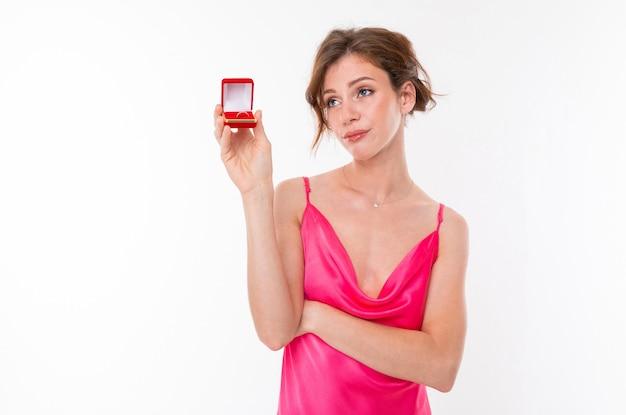 Junges schönes mädchen mit gewelltem braunem geflicktem haar, sauberer haut, flachen zähnen, schönem lächeln, im rosa trikot, hält eine trainingsringbox und denkt Premium Fotos