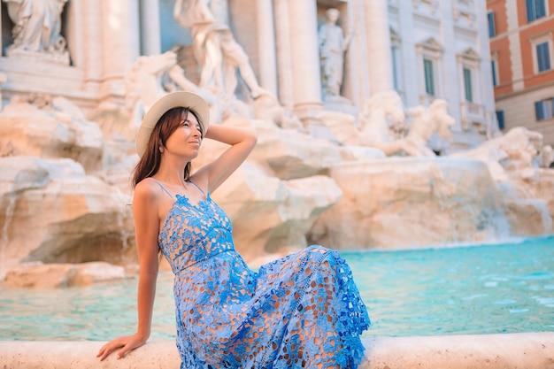 Junges schönes mädchen nahe brunnen fontana di trevi mit stadtplan Premium Fotos