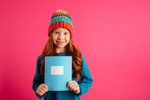 Junges schönes mädchen, welches das blaue exemplarbuch und -c $ lächeln getrennt zeigt Kostenlose Fotos