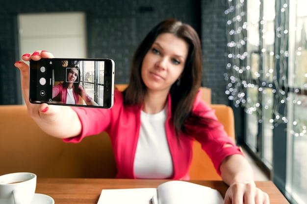 Junges schönes mädchen, welches das selfie sitzt im café tut. Premium Fotos