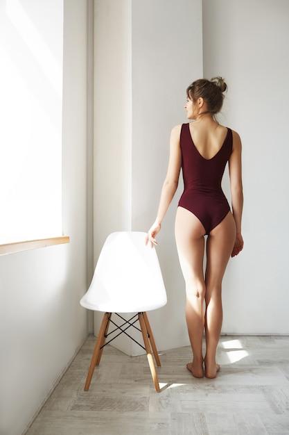 Junges schönes modell in der badebekleidung, die fenster betrachtet, das morgensonnenlicht genießt, das nahe stuhl nahe weißer wand zurücksteht. Kostenlose Fotos