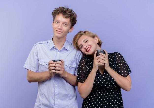 Junges schönes paar mann und frau, die zusammenhalten kaffeetassen halten, die fröhlich über der blauen wand stehend lächeln Kostenlose Fotos