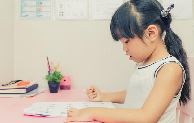 Junges schulmädchen, das zu hause ein buch mit weinlesefarbeffekt liest Premium Fotos