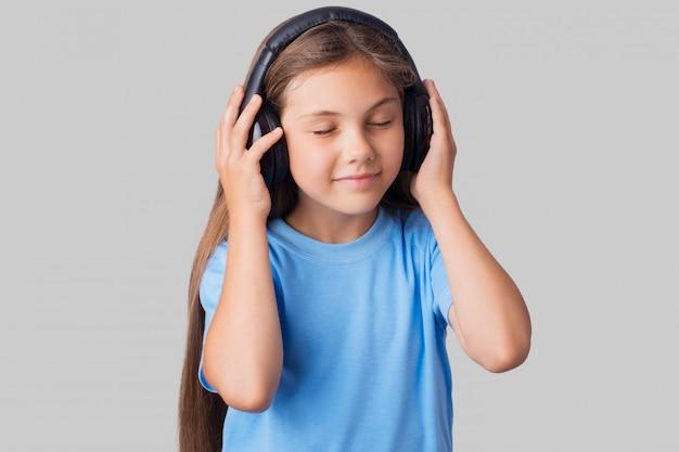 Junges schulmädchen im blauen t-shirt mit kabellosen kopfhörern zum musikhören Premium Fotos
