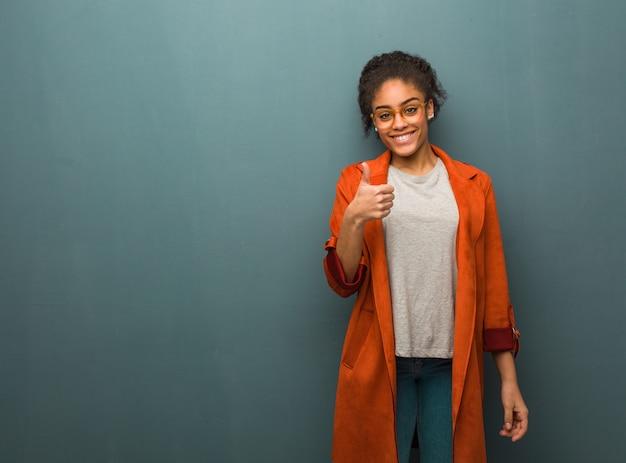 Junges schwarzafrikanermädchen mit blauen augen oben lächelnd und daumen anhebend Premium Fotos