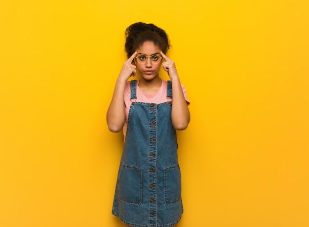 Junges schwarzafrikanermädchen mit den blauen augen, die eine konzentrationsgeste tun Premium Fotos