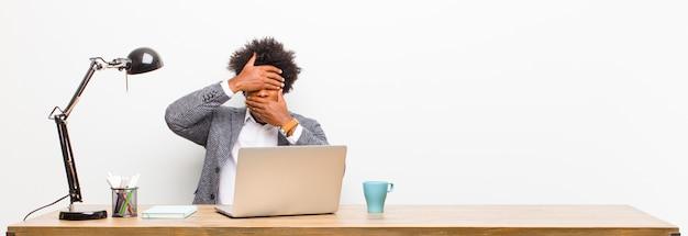 Junges schwarzes geschäftsmannbedeckungsgesicht mit beiden händen Premium Fotos