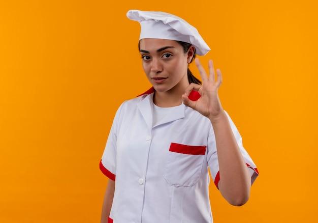 Junges selbstbewusstes kaukasisches kochmädchen in der kochuniform gestikuliert ok handzeichen lokalisiert auf orange wand mit kopienraum Kostenlose Fotos