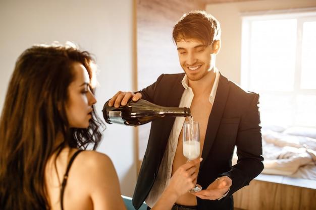 Junges sexy paar im wohnzimmer. fröhlicher netter geschäftsmann im anzug, der sekt in das glas der frau gießt. zusammen im raum. sexy souple nach intimität. Premium Fotos