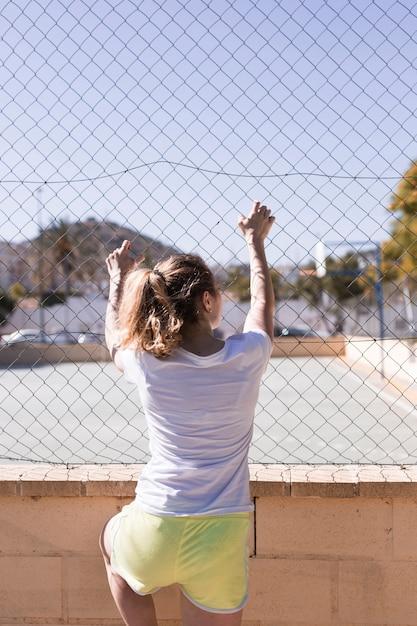 Junges sportives mädchen, das auf metallzaun hält Kostenlose Fotos