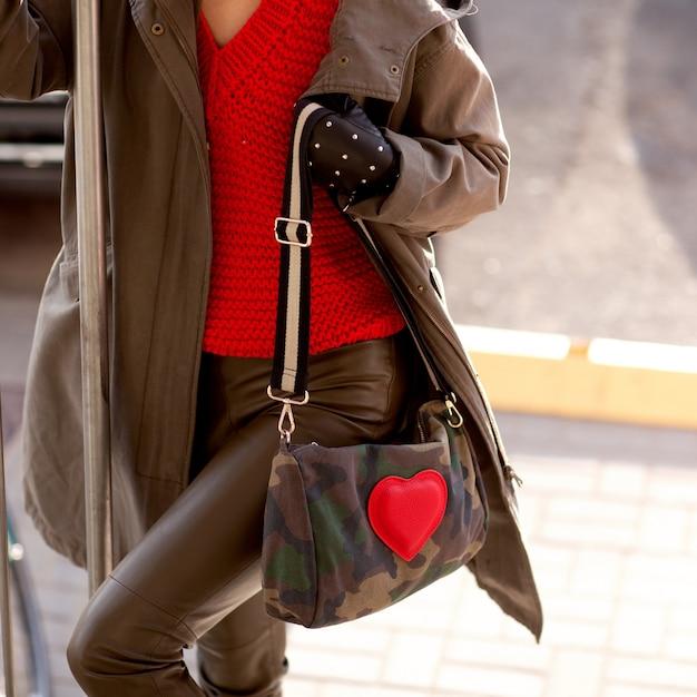Junges stilvolles mädchen in den lederhosen, in einer roten strickjacke und in den händen einer hellen tasche Premium Fotos