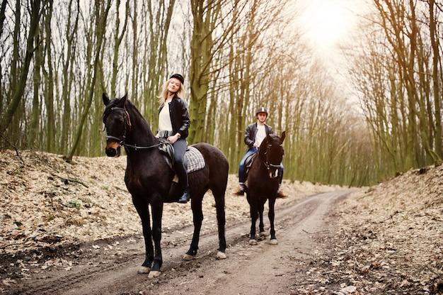 Junges stilvolles paarreiten auf pferden am herbstwald Premium Fotos