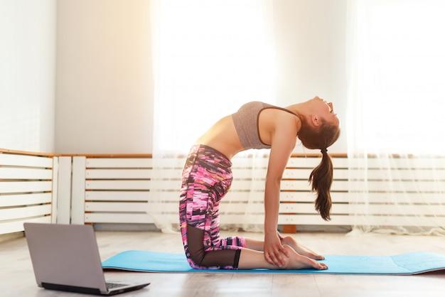 Junges süßes mädchen praktiziert yoga zu hause, nimmt posen ein und schaut auf einen laptop Premium Fotos