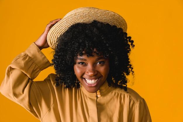 Junges toothy lächeln der schwarzen frau und halten des strohhutes Kostenlose Fotos
