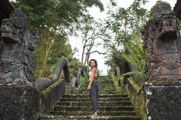 Junges touristisches mädchen, das in camera schaut, bleibend auf alter steinbalinesse treppe Premium Fotos