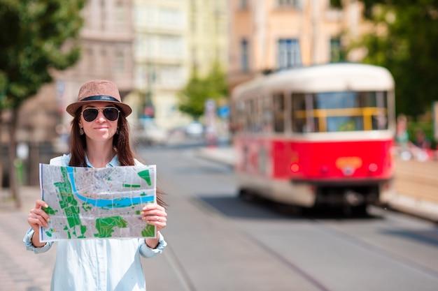 Junges touristisches mädchen mit einem stadtplan, der draußen anziehungskraft sucht. kaukasische frau der reise mit karte draußen während der feiertage in europa. Premium Fotos