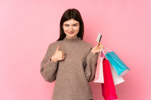 Junges ukrainisches jugendlichmädchen über der lokalisierten rosa wand, die einkaufstaschen und eine kreditkarte hält Premium Fotos