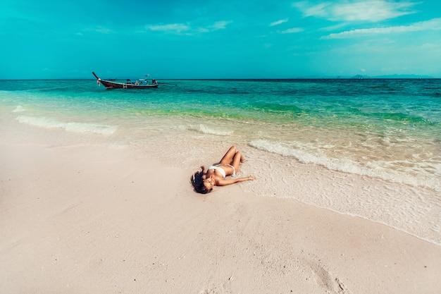 Junges und hübsches mädchenmodell in einem bikini, der auf dem strandurlaubsort der andamanensee ein sonnenbad nimmt Premium Fotos