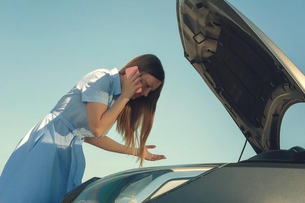 Junges und schönes mädchen nahe einem defekten auto mit einer offenen haube. probleme mit dem auto, startet nicht, funktioniert nicht. Premium Fotos