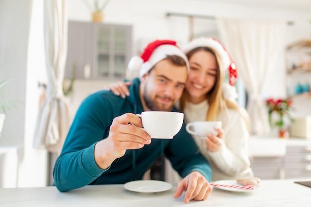 Junges verheiratetes paar in den weihnachtshüten trinkt kaffee in der küche Premium Fotos