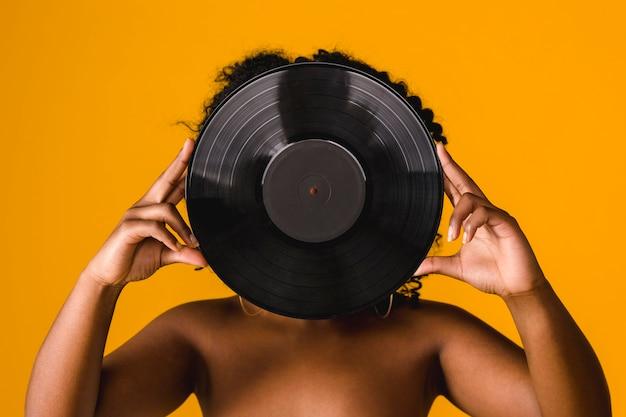 Junges weibliches bedeckungsgesicht des nackten afroamerikaners mit vinylplatte im studio Kostenlose Fotos