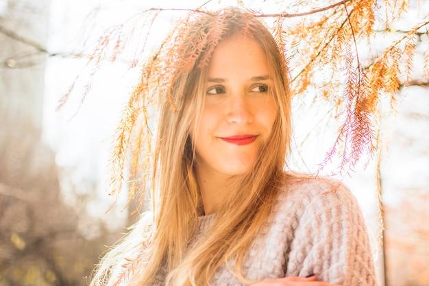 Junges weibliches lächeln beiseite auf herbstoberfläche Kostenlose Fotos