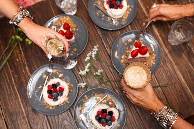 Junggesellenabschied, mädchenhände mit getränken und süßen kuchen mit sommerbeeren auf einem holztisch. party, süßer tisch. sommer bieten desserts im restaurant. Premium Fotos