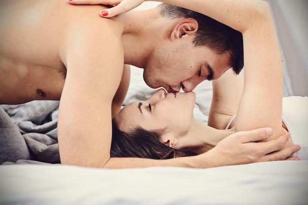 Jungvermählten, die leicht am frühen morgen im bett küssen Premium Fotos