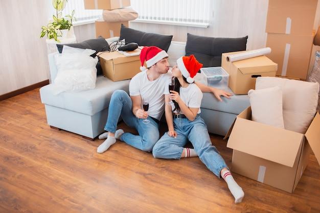 Jungvermählten feiern weihnachten oder neujahr in ihrer neuen wohnung. junger glücklicher mann und frau trinken wein, feiern umzug in ein neues zuhause und sitzen zwischen kisten. Premium Fotos