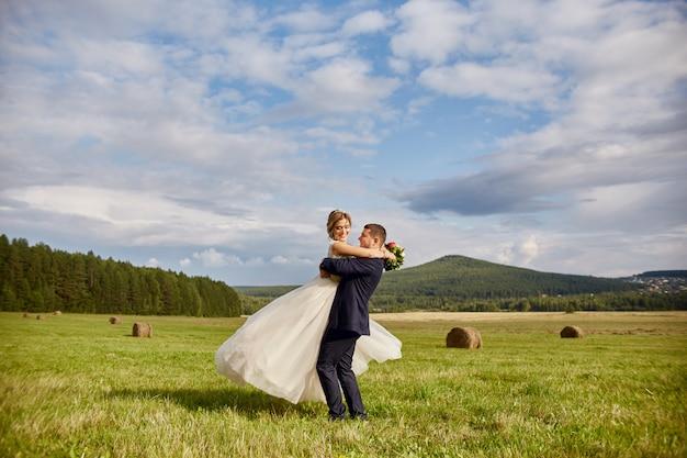 Jungvermählten gehen und entspannen sich auf dem gebiet und heiraten Premium Fotos