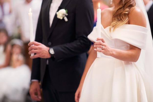 Jungvermählten stehen mit kerzen während der verlobungszeremonie in der kirche Kostenlose Fotos