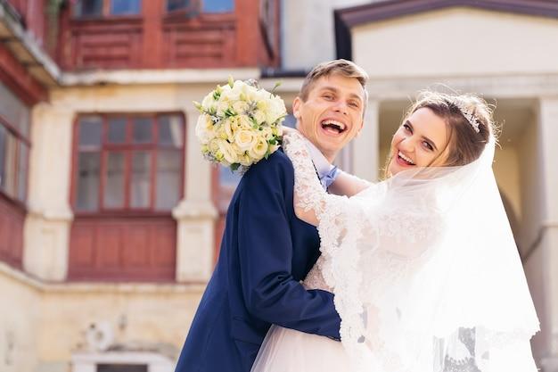Jungvermählten umarmen sich und schauen in die kamera Premium Fotos