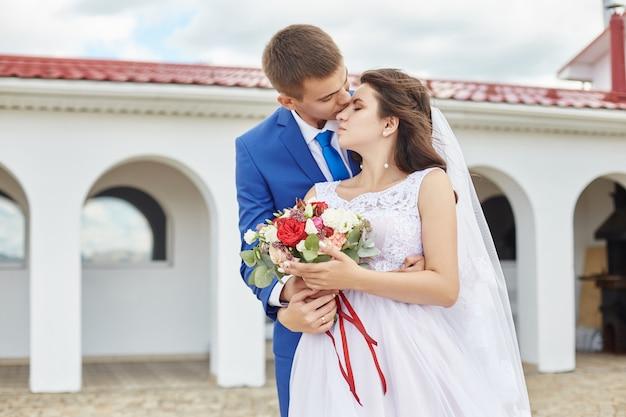 Jungvermählten umarmen und küssen nahe leuchtturm an der hochzeit Premium Fotos