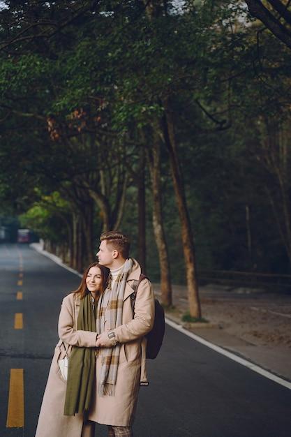 Jungvermähltenpaare, die neigung und händchenhalten zeigen, wie sie durch den nationalen forest park zhangjiajie gehen Kostenlose Fotos