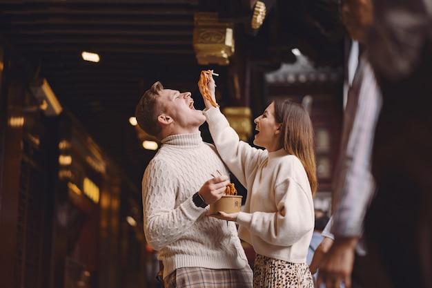 Jungvermähltenpaare, die nudeln mit essstäbchen in shanghai außerhalb eines lebensmittelmarktes essen Kostenlose Fotos