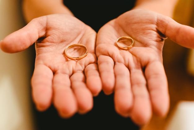 Jungvermähltenringe in den händen der braut und des bräutigams. Premium Fotos