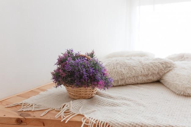 Jute-korb mit lila blumen bretterboden mit gestrickten kissen und bezug Kostenlose Fotos