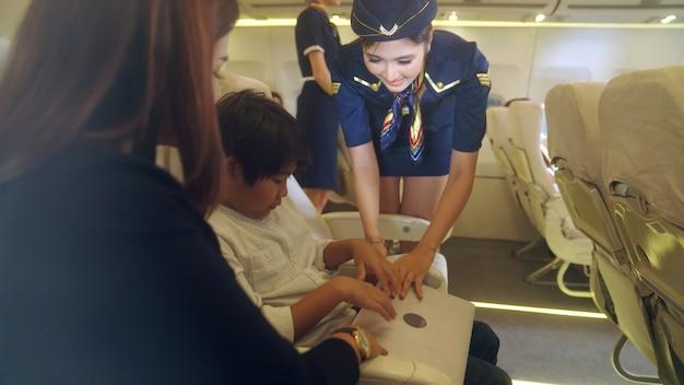 Kabinenpersonal, das der familie im flugzeug dienst leistet Premium Fotos