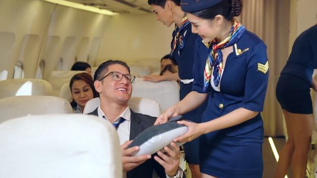 Kabinenpersonal, das einem passagier ein kissen gibt Premium Fotos