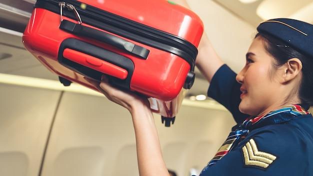 Kabinenpersonal heben gepäcktasche im flugzeug an Premium Fotos
