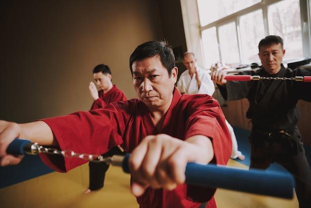 Kämpfer in verschiedenen farben keikogi-training mit nunchuck. Premium Fotos