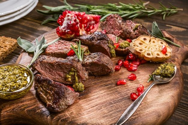 Kängurufleischsteak mit grünem pesto und granatapfel auf hölzernem schneidebrett. Premium Fotos