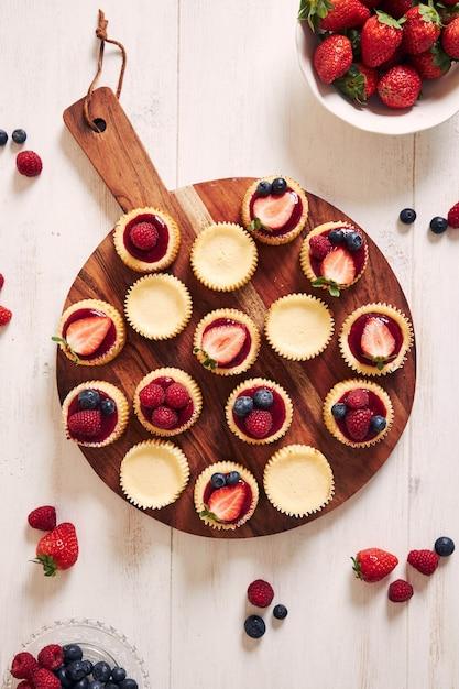 Käse cupcakes mit fruchtgelee und früchten auf einem holzteller Kostenlose Fotos
