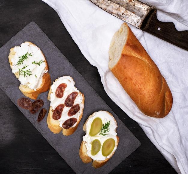 Käse der sandwiche mit sahne auf schwarzem Premium Fotos